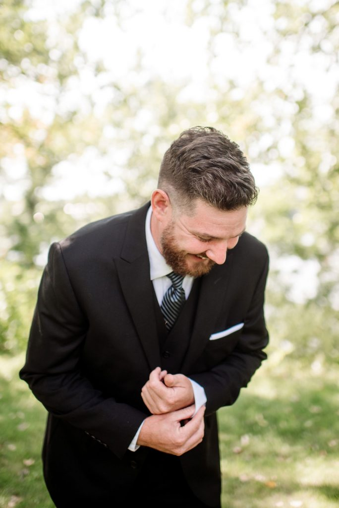 groom in minneapolis park before wedding sunny summer day