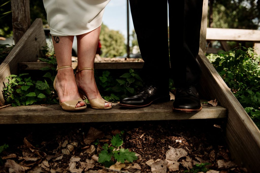 Bride's high heeled shoes and groom's dapper shoes at wedding ceremony at glueks park northeast minneapolis summer day