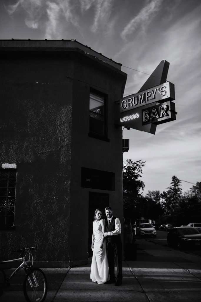 Black and white image couple at night outside grumpys bar northeast minneapolis dive bar wedding